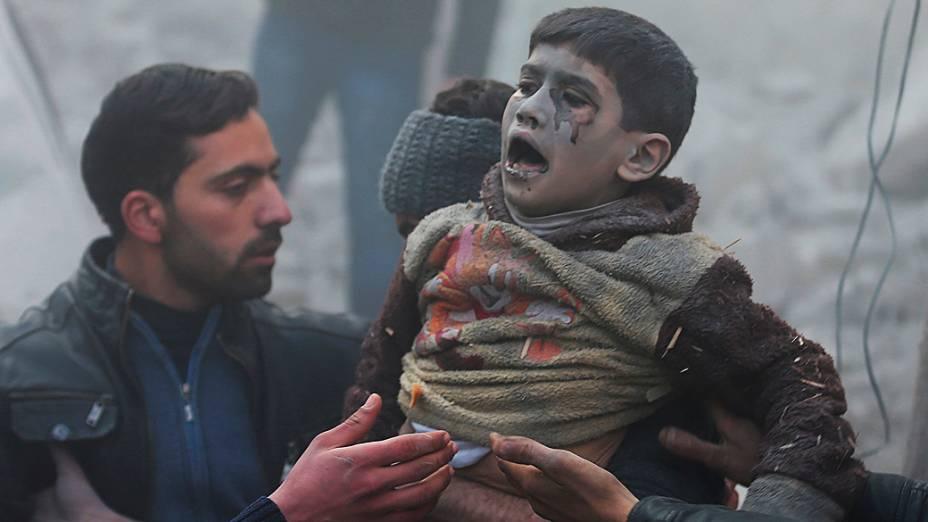 Menino resgatado com vida após bombardeio ao distrito de Duma, em Damasco (Síria)