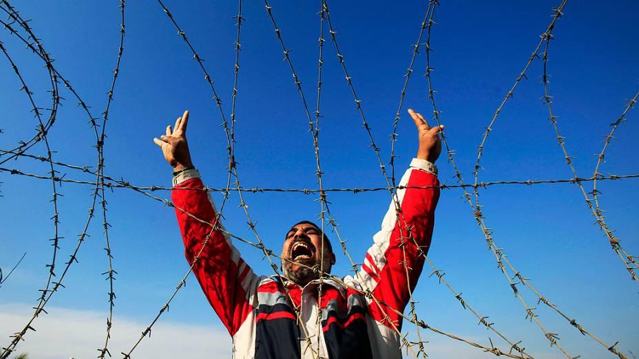 Manifestante protesta em frente de uma barreira montada em tribunal no Cairo, nesta quarta-feira (08). O julgamento ex-presidente do Egito Mohamed Morsi foi adiado pela segunda vez consecutiva e será realizado no próximo dia 1º de fevereiro