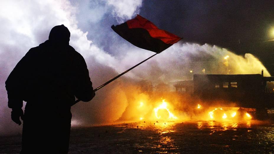 Manifestante segura a bandeira da Ucrânia em frente a um grupo de policiais durante protesto em Kiev, na madrugada desta segunda-feira (20)