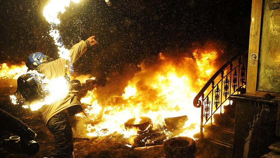 Manifestante lança coquetel molotov em confronto com a polícia durante protesto contra o governo em Kiev, na Ucrânia
