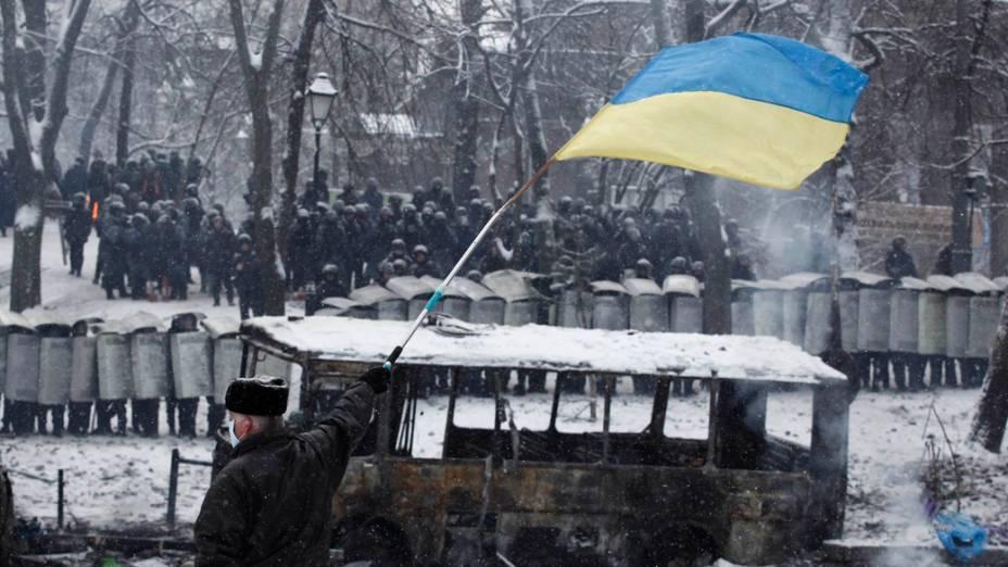 Ucraniano abana bandeira em frente a tropa de choque durante confrontos com manifestantes pró-Europa, em Kiev