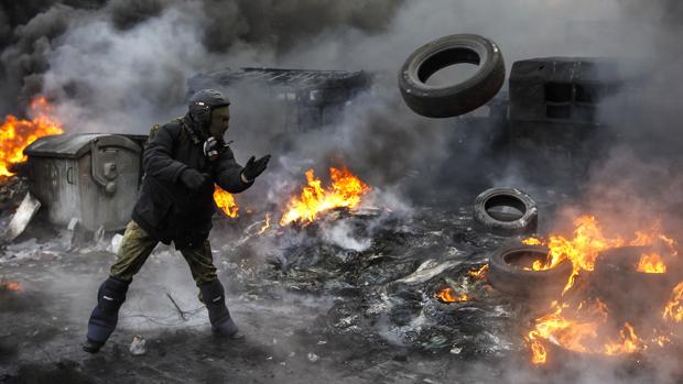 Em Kiev, manifestante pró-Europa lança pneu em barricada