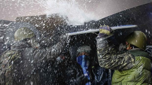 Manifestantes pró-Europa se protegem de jato dàgua lançado pela policia, em Kiev