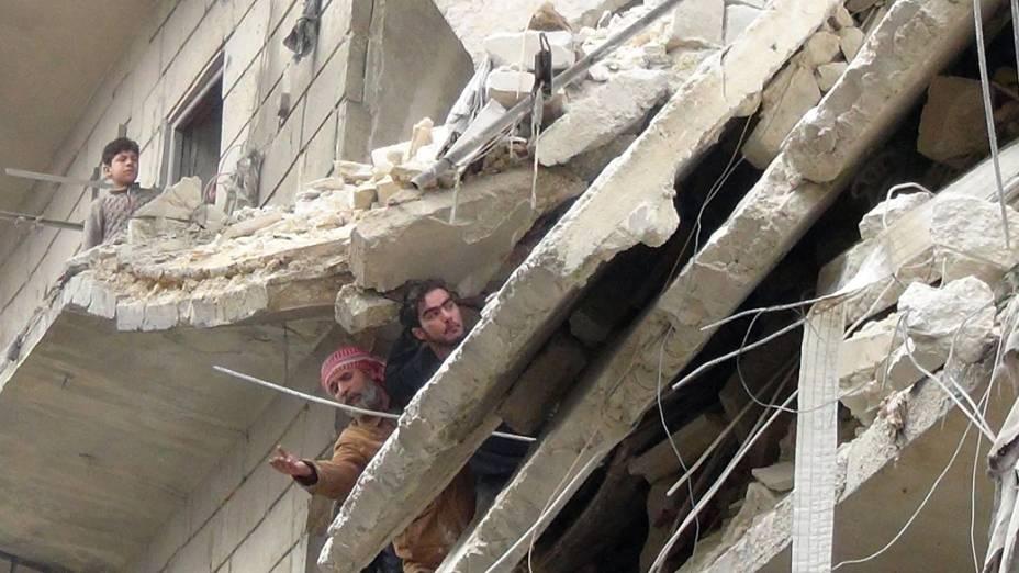 Sírios em um prédio após ataque aéreo no norte da cidade de Aleppo