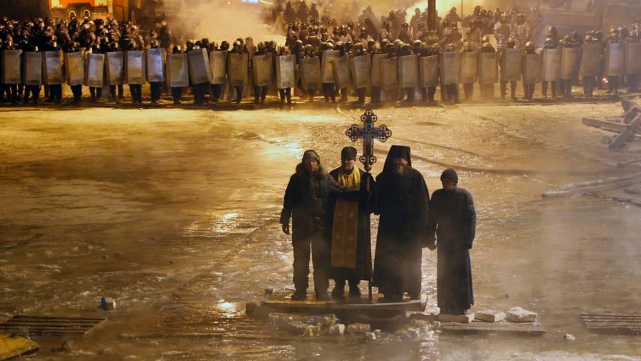 Padres ortodoxos rezam entre os ativistas pró-europeus e linhas de policiais no centro de Kiev, na Ucrânia
