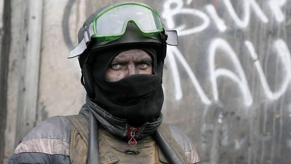 Manifestante guarda as barricadas em frente da polícia anti-motim em Kiev, Ucrânia