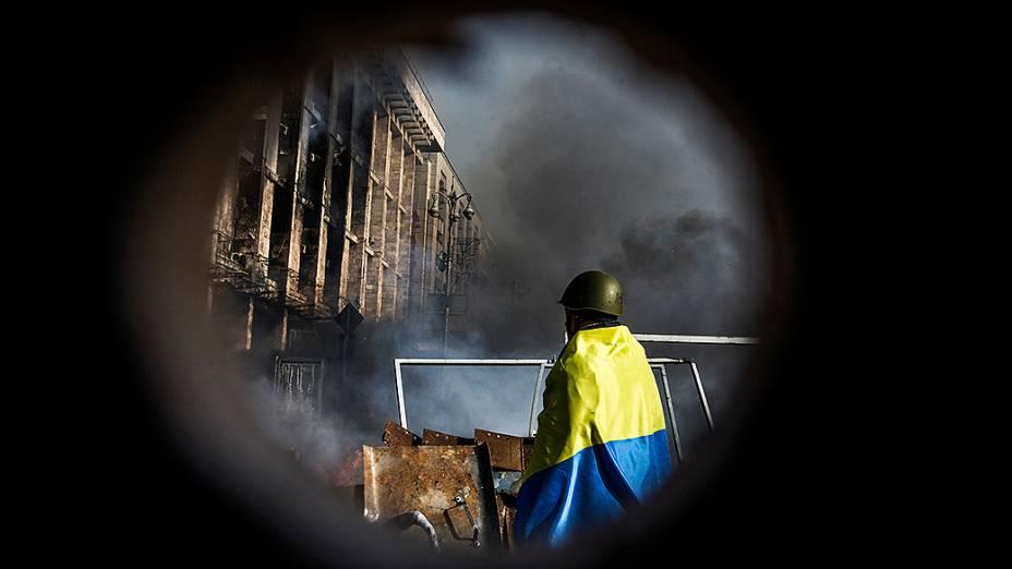 Manifestante anti-governo com a bandeira ucraniana caminha próximo a uma barricada durante confrontos com a polícia na praça da Independência em Kiev