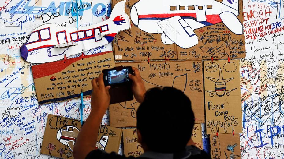 <p>Homem tira foto de desenhos de aviões em homenagem ao voo desaparecido em mural no aeroporto de Kuala Lumpur na Malásia</p>