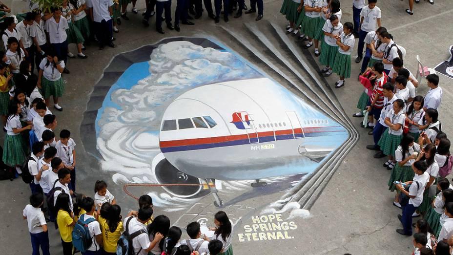 <p>Estudantes se reúnem em torno de obra de arte tridimensional, baseada no voo 370 da Malaysia Airlines, desaparecido desde 8 de março, pintada em Makati (Filipinas)</p>