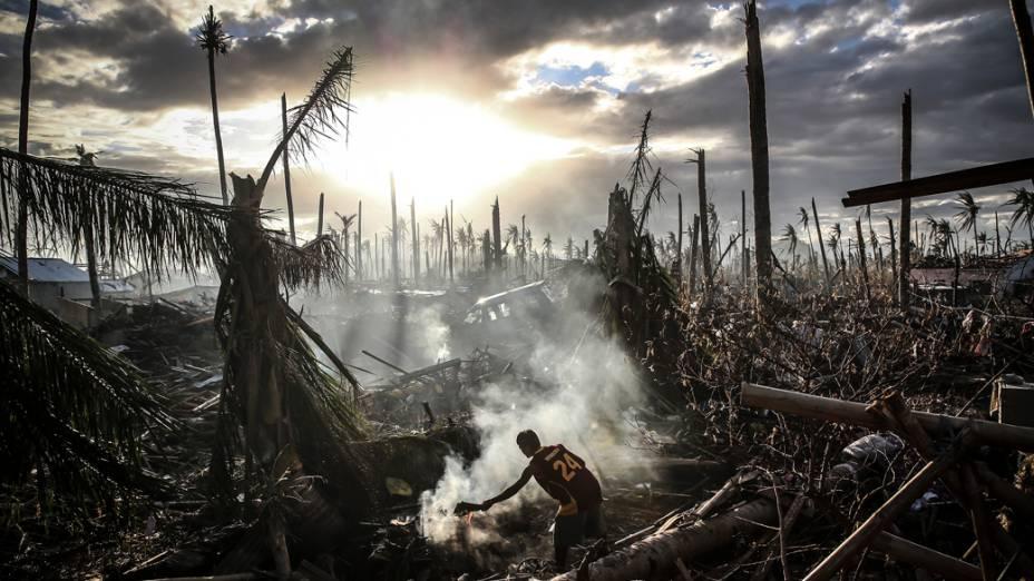 Homem tenta apagar um pequeno foco de incêndio em meio à destruição causada pela passagem do supertufão Haiyan em Leyte, nas Filipinas