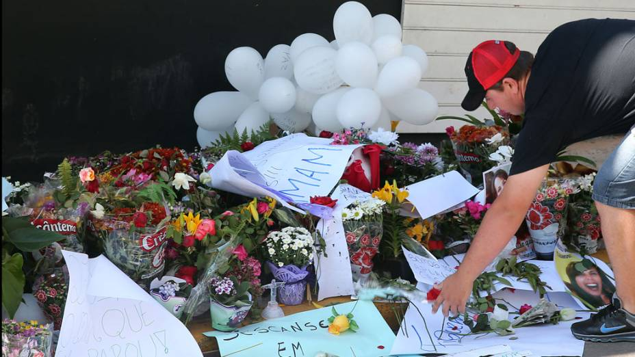 Um homem coloca flores em frente a boate Kiss em homenagem as vítimas da tragédia