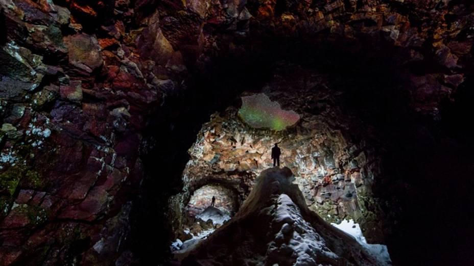 <p>Imagem feita em uma caverna de lava de 1.300 metros na Islândia. O teto cedeu em algumas partes, o que faz com que a neve se  acumule lá dentro durante o inverno. Um buraco no telhado, na parte superior da foto, revela uma aurora boreal no céu</p>