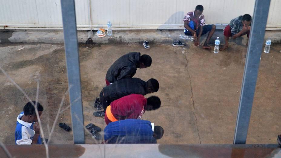 Imigrantes detentos rezam no abrigo temporário em Lampedusa