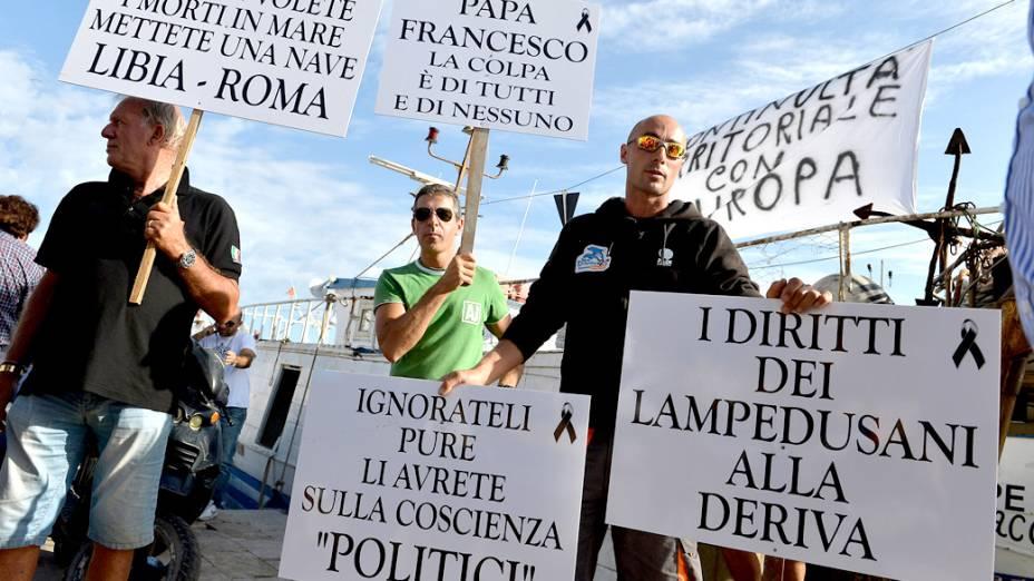 Ativistas protestam do lado de fora do aeroporto de Lampedusa, durante a visita de Manuel Barroso, Presidente da Comissão Europeia