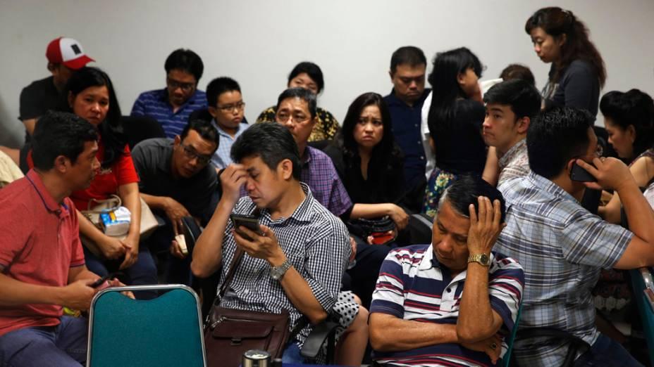 Familiares de passageiros do avião da AirAsia no aeroporto de Surabaya na Indonesia
