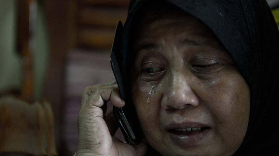 <p>Familiar de passageiros do voo da Malaysia Airlines, que desapareceu no Mar da China Meridional, chora ao telefone no Aeroporto Internacional de Kuala Lumpur, na Malásia</p>
