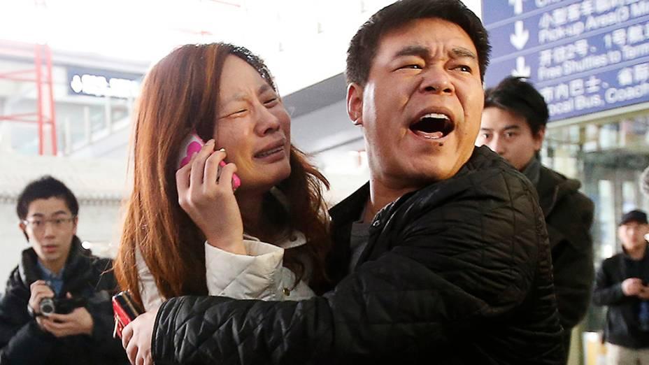 <p>Mulher chora enquanto fala ao celular em busca de informações de um parente que estava no avião da Malaysia Airlines e desapareceu no Mar da China Meridional, no Aeroporto Internacional de Pequim</p>