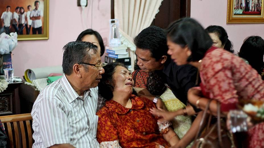 <p>Familiares de um cidadão indonésio que estava no voo da Malaysia Airlines que desapareceu sobre o Mar do Sul da China, em sua residência em Medan, na Indonésia</p>