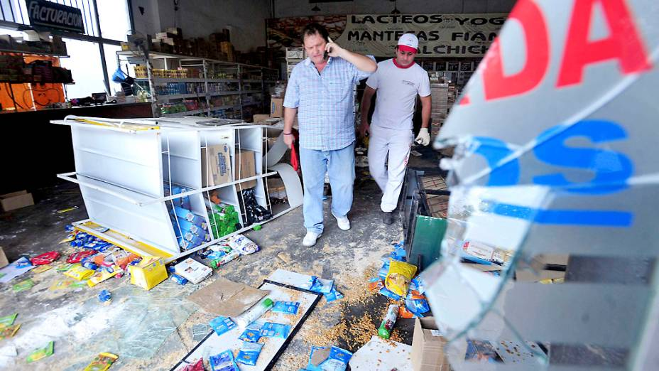 Dono de um mercado avalia os prejuízos após ter seu estabelecimento saqueado na província de Tucuman, na Argentina