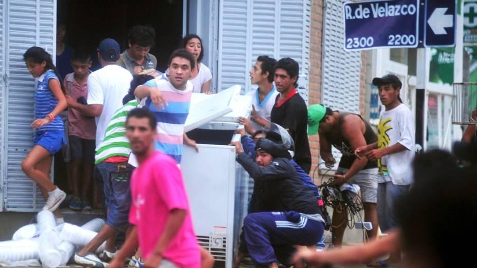 Pessoas carregam produtos após saquearem um mercado na província de Tucuman, na Argentina