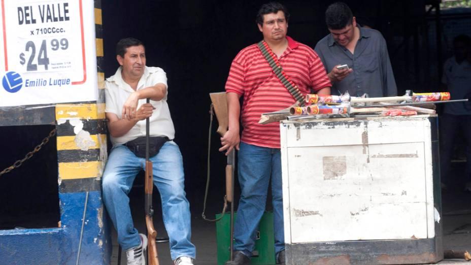 Funcionários de um mercado se armam para proteger um estabelecimento na província de Tucuman, na Argentina