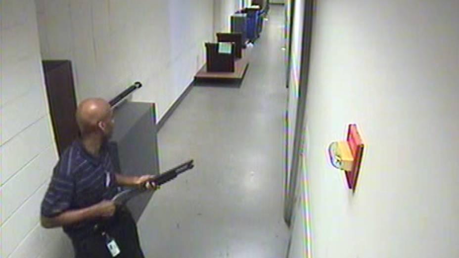 Alexis Aaron caminhando pelos corredores do prédio da Marinha carregando uma escopeta Remington 870. Ao abrir fogo, ele fez doze vítimas, antes de ser morto pela polícia.