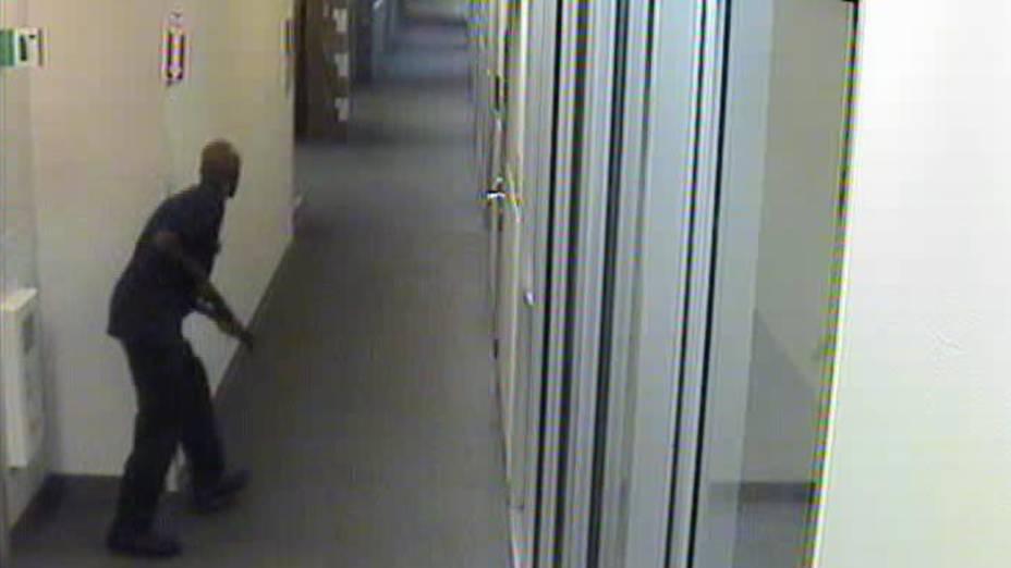 Alexis Aaron caminhando pelos corredores do prédio da Marinha carregando uma escopeta Remington 870