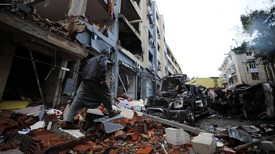 Homem caminha entre os escombros de uma rua onde um carro-bomba explodiu, em Reyhanli, em Hatay, a poucos quilômetros da fronteira com a principal passagem para a Síria, na Turquia