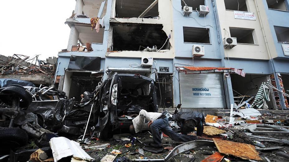 Homens olham debaixo de um carro destruído em uma rua onde um carro-bomba explodiu deixando mais de 43 mortos, em Reyhanli, em Hatay, a poucos quilIômetros da fronteira com a principal passagem para a Síria