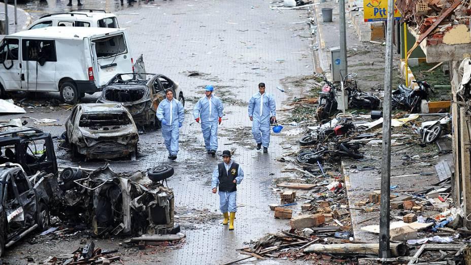 Policiais prestam socorro em uma rua destruída por uma explosão de carro-bomba que atingiu Hatay deixando mais de 43 mortos, a poucos quilômetros da fronteira com a principal passagem para a Síria