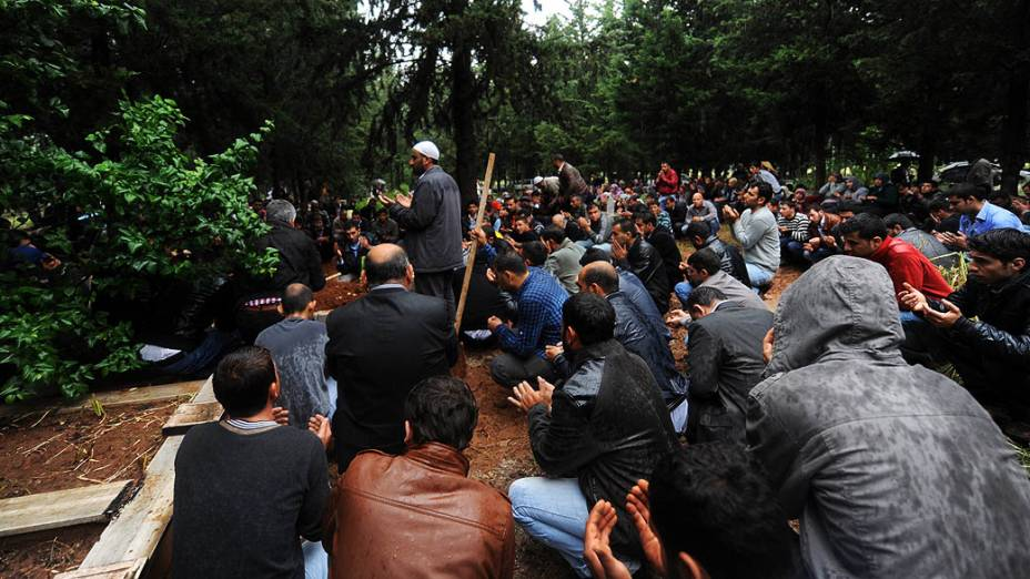 Homens fazem orações nas sepulturas das vítimas de um carro-bomba que explodiu em Hatay apenas alguns quilômetros da principal passagem de fronteira para a Síria