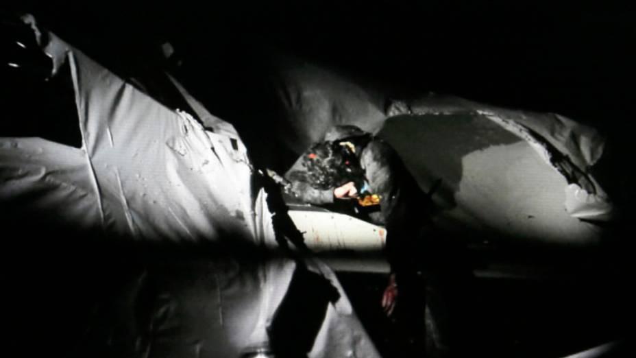 Dzhokhar Tsarnaev, com o ponto vermelho da mira de um rifle de um atirador no topo de sua cabeça, inclina-se sobre uma parte de um barco onde ele estava se escondendo momentos antes de sua captura pelas autoridades policiais em Watertown, Massachusetts pela atentado a bomba na Maratona de Boston