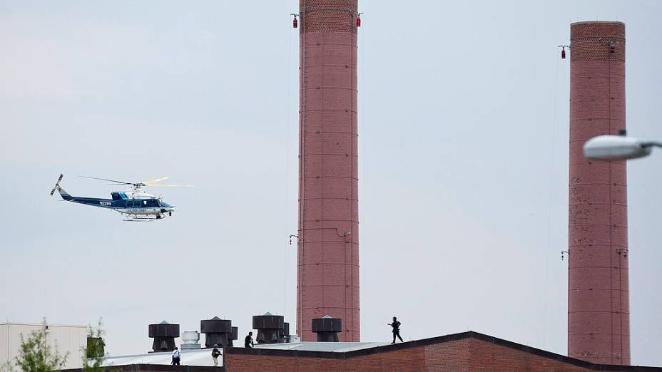 Um helicóptero da polícia sobrevoa o telhado de um edifício em resposta a um tiroteio no Arsenal de Marinha de Washington, nesta segunda-feira (16)