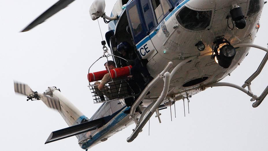 Um helicóptero da polícia levanta o que parece ser uma vítima do tiroteio enquanto sobrevoa o telhado do edifício da Marinha em Washington