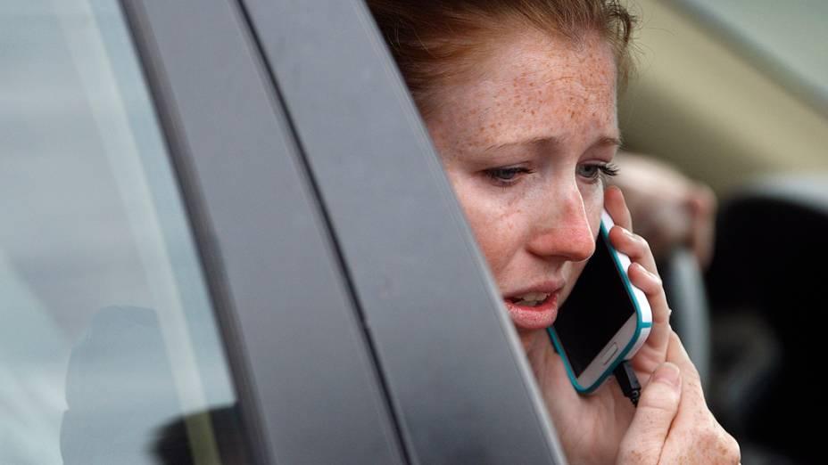 Familiar de um trabalhador do Arsenal da Marinha, fala ao telefone em busca de informações em um abrigo improvisado no estádio de beisebol Nationals Park, perto da instalação naval em Washington
