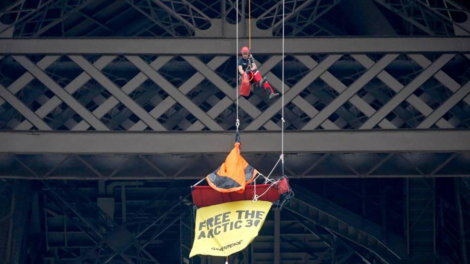 Bombeiro se aproxima de um ativista do Greenpeace pendurado no segundo andar da Torre Eiffel, que protestava contra as 30 pessoas detidas na Rússia após uma manifestação do grupo