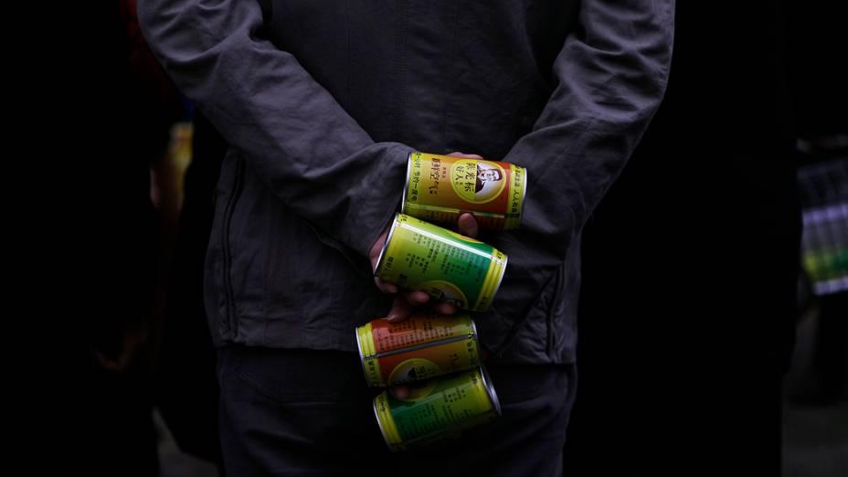Homem segura latas de ar fresco que foram dadas pelo chinês multimilionário Chen Guangbiao no centro de Pequim, China