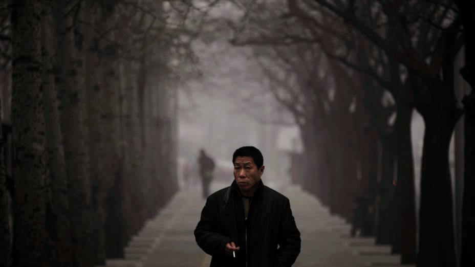 Homem anda ao longo de uma rua em dia nebuloso em Pequim, China