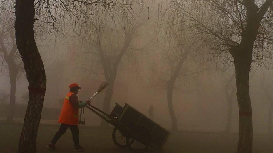 Trabalhador chinês em um parque de Pequim, vestindo máscara para se proteger da poluição, na manhã desta quarta-feira (30)