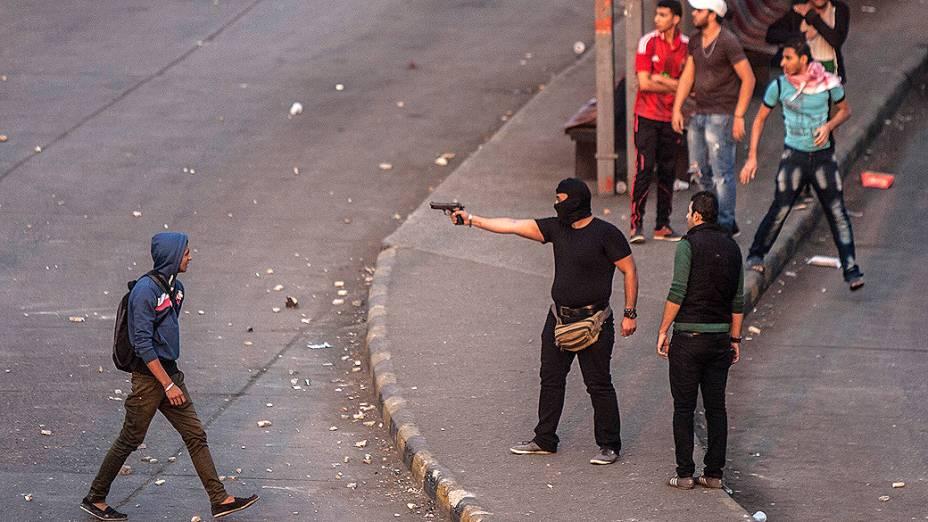 Manifestante mascarado aponta uma arma durante protestos que lembram o aniversário dos atos de 2011 quando dezenas de manifestantes foram mortos nos arredores da Praça Tahrir, no Cairo, após a queda do então presidente Mubarak - (19/11/2013)