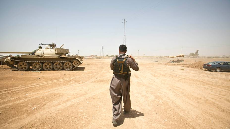 Na aldeia iraquiana de Basheer, membro das forças curdas passa por um tanque durante uma pausa nos combates contra militantes sunitas liderados pelo Estado Islâmico do Iraque e do Levante (ISIL)