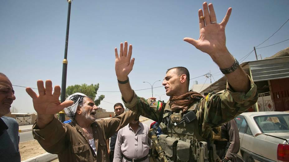 Soldado das forças curdas Peshmerga fala com um líder de uma comunidade xiita local, que elogia ações das Forças Especiais curdos para protegê-los de militantes sunitas liderados pelo Estado Islâmico do Iraque e do Levante (ISIL), na cidade de Kirkuk
