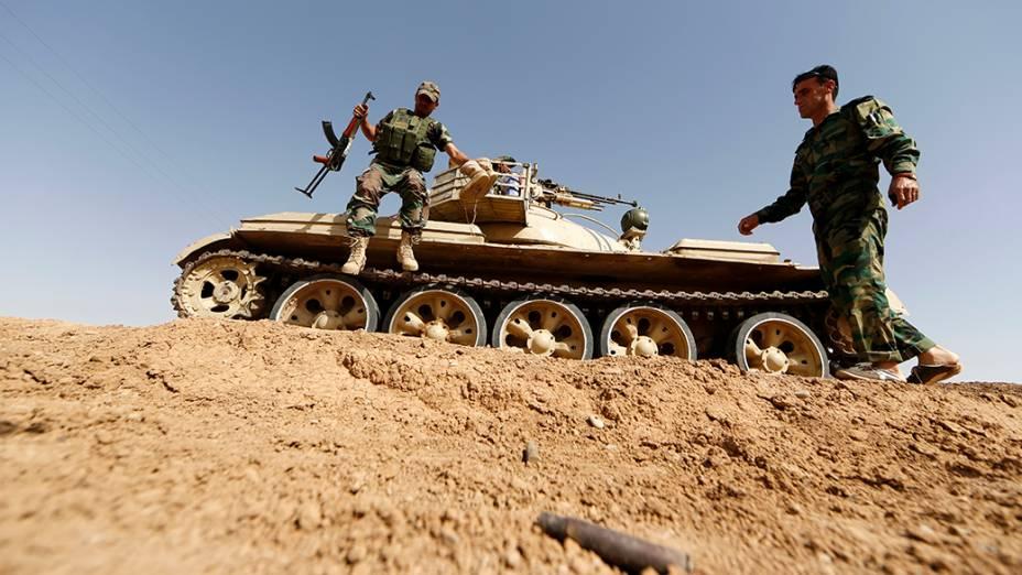 Membros das forças curdas Peshmerga mantém posição na aldeia iraquiana de Basheer; Militantes sunitas liderados pelo Estado Islâmico do Iraque e do Levante assumiram o controle de uma passagem de fronteira Iraque-Síria depois que os rebeldes sírios se retiraram durante a última madrugada