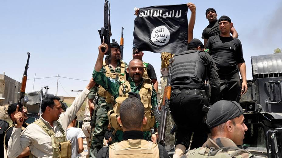 Forças de segurança iraquianas destroem a bandeira do grupo militante sunita pertencente ao Estado Islâmico do Iraque e do Levante (EIIL), durante uma patrulha na cidade de Dalli Abbas; O líder da Al Qaeda pediu aos muçulmanos de todo o mundo para pegarem em armas e migram para o Estado declarado em solo sírio e iraquiano