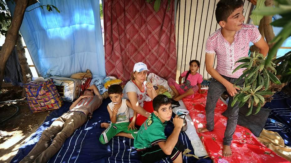 Cristãos iraquianos que fugiram da violência da cidade de Qaraqosh descansam próximo à uma Igreja, no iraque