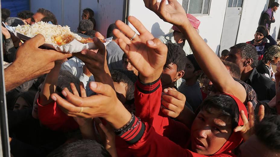Iraquianos desabrigados se aglomeram para receber comida de curdos, na Síria
