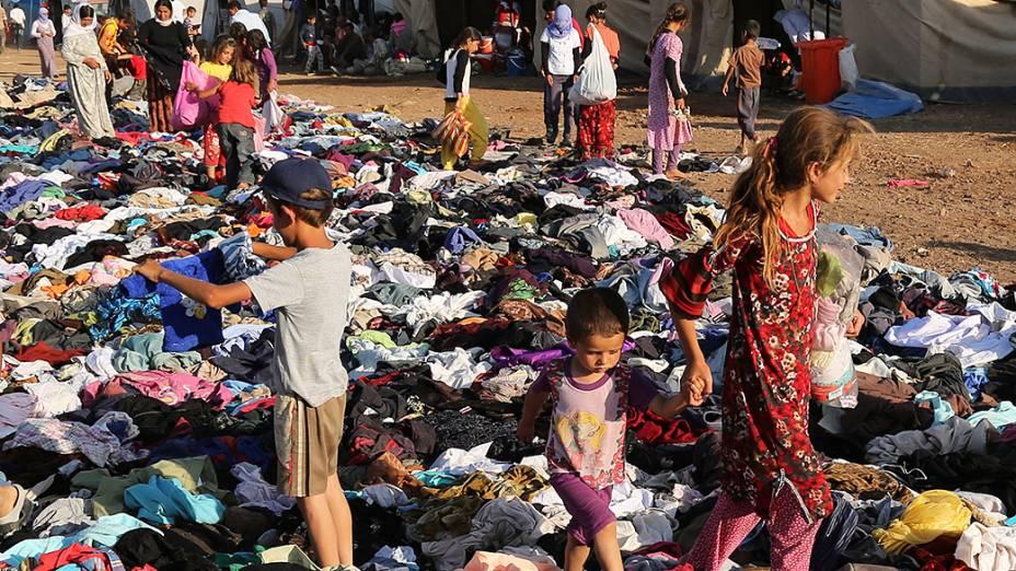 Iraquianos desabrigados recebem doações de roupas, na Síria