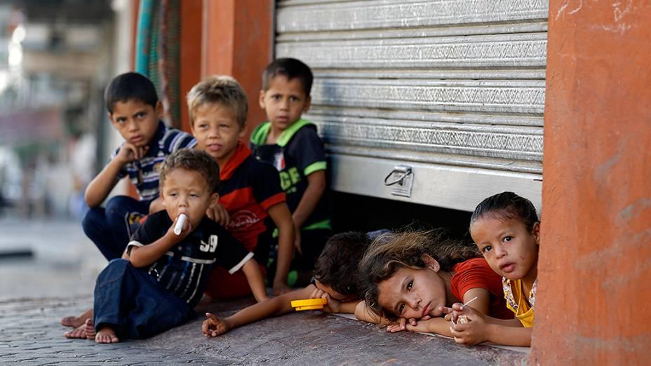 Crianças palestinas fotografadas debaixo da porta de uma loja onde estão abrigadas com sua família, na cidade de Gaza - 26/07/2014