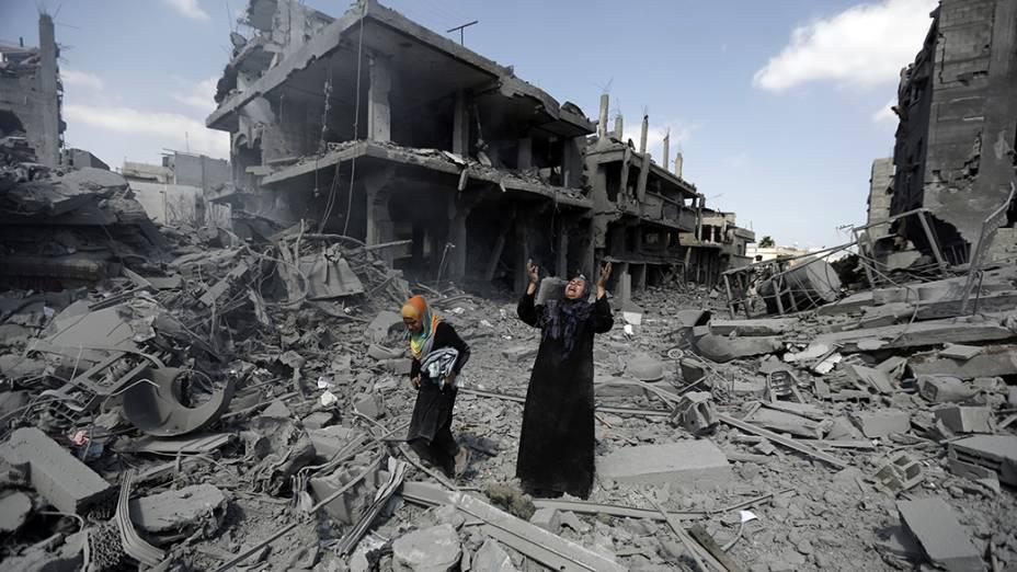 Mulher caminha em meio a edifícios destruídos por bombardeios israelenses no distrito de Beit Hanoun na Faixa de Gaza durante trégua humanitária