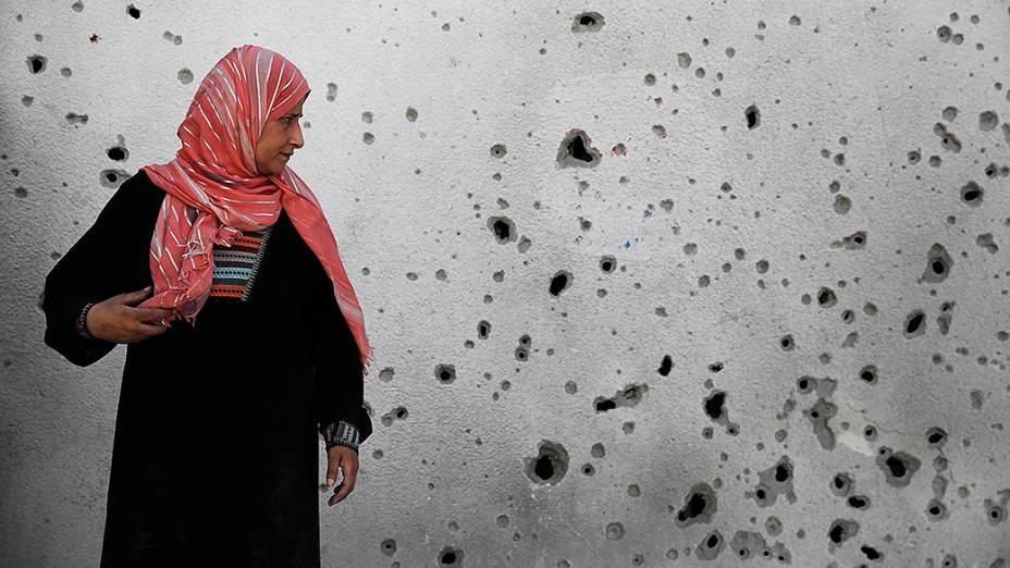 Mulher olha para uma parede com marcas de estilhaços após um ataque aéreo israelense no hospital de Beit Hanoun, em Gaza